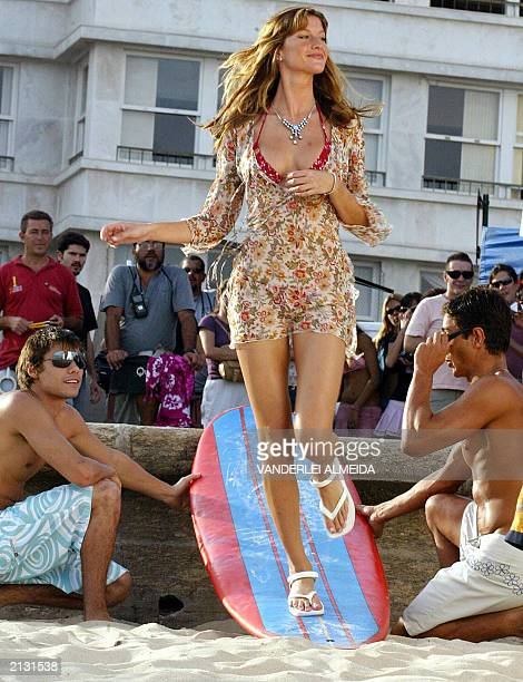 Brazilian top model Gisele Bundchen walks over a surfboard during the taping of a TV commercial to promote a line of sandals bearing her name at...