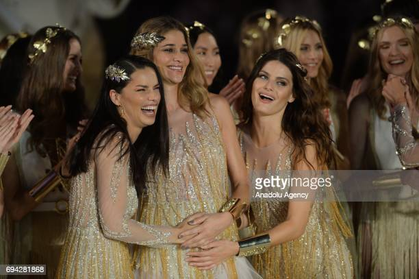 Brazilian top models Adriana Lima Isabeli Fontana pose with pregnant Brazilian model Ana Beatriz Barros as they salute the people at the runway...