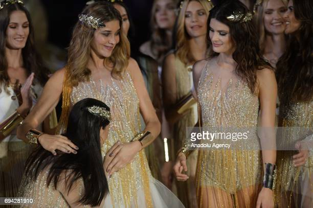 Brazilian top models Adriana Lima kisses the belly of pregnant Brazilian model Ana Beatriz Barros as they salute the people with Brazilian model...