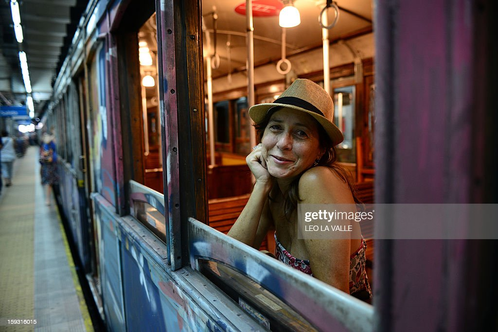 A Brazilian tourist poses for a picture on a Le Burgeoise wagon of the A Line subway, in Buenos Aires, on January 11, 2013 during the so called last ride of the historic trains. The Line A will be closed betwen January 12 and March 8 following a decision by Buenos Aires city Mayor Mauricio Macri to replace the fleet with Chinese-made wagons. Line A was the first subway line to work in the southern hemisphere and its trains are among the ten oldest still working daily. The La Brugeoise wagons were constructed between 1912 and 1919 by La Brugeoise et Nicaise et Delcuve in Belgium. AFP PHOTO/Leo La Valle