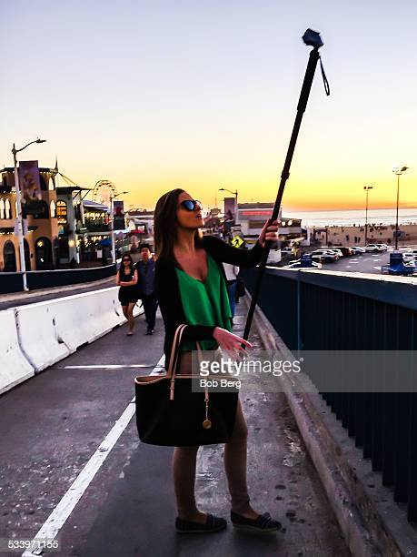 Santa Monica Ca January 16 2015 A Brazilian tourist takes a selfie with a selfie stick on the walkway approach to the Santa Monica pier