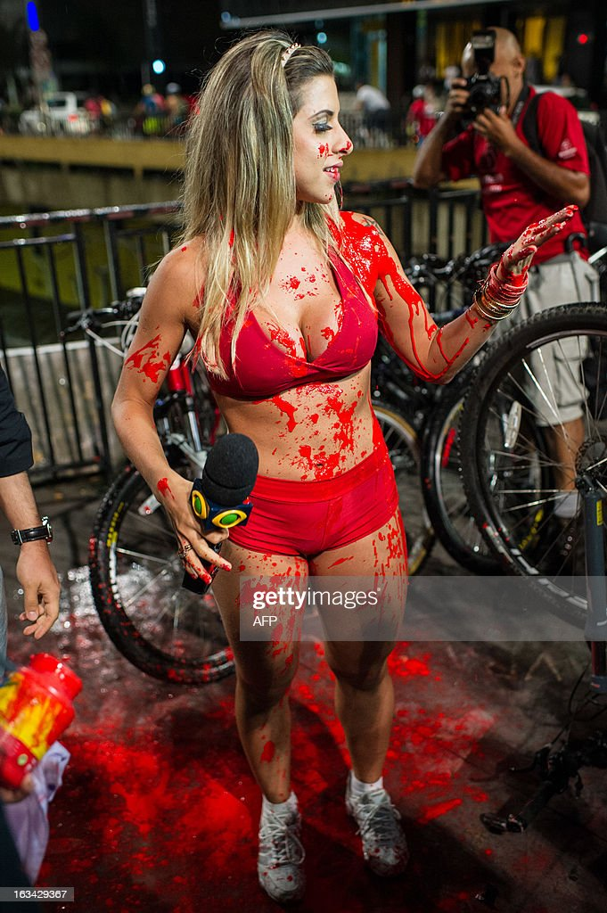 Brazilian TV celebrity Ana Paula Minerato holds a microphone after being thrown red paint by a cyclist who refused her presence in the 6th 'Naked Pedalling', an annual cycling event, at Paulista Avenue in Sao Paulo, Brazil, on March 9, 2013. The event welcomes naked cyclists to celebrate cycling and the human body and protest against cars, gas emission and agressive drivers. AFP PHOTO/Yasuyoshi CHIBA