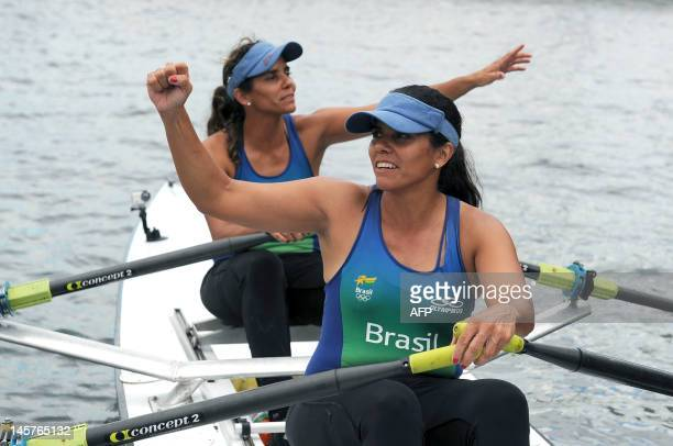 Brazilian twin sisters Claudia and Katia Alencar former members of Brazil's rowing team cheer after arriving on their double scull boat at Guanabara...