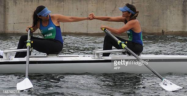 Brazilian twin sisters Claudia and Katia Alencar former members of Brazil's rowing team rejoice after arriving on their double scull boat at...