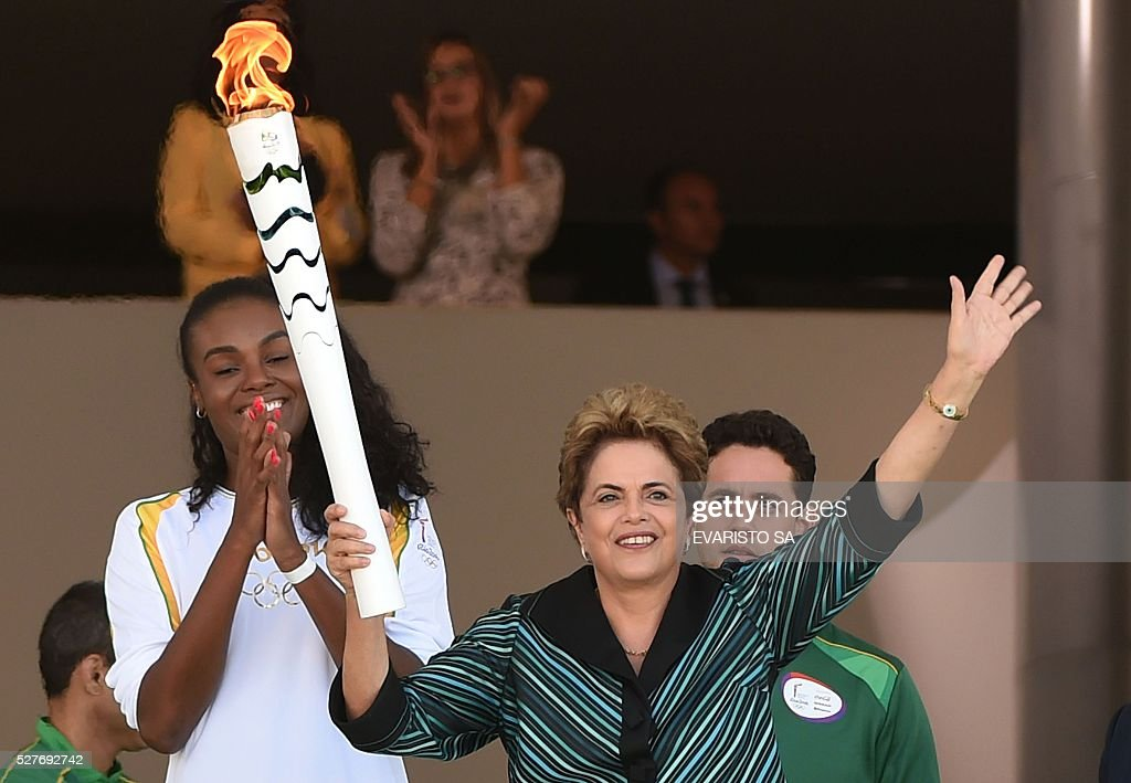 Brazilian volleyball player Fabiana Claudino (L) applauds as Brazilian President Dilma Rousseff holds the Olympic torch at Planalto Palace in Brasilia following the flame's arrival in the country on May 3, 2016 ahead of the Rio 2016 Olympic Games in August. The Olympic flame arrived in Brasilia May 3 aboard a flight from Geneva to embark on a procession across Brazil culminating in the opening ceremony of the 2016 Games in Rio de Janeiro. The torch will travel to more than 300 towns and cities carried by some 12,000 relay runners before arriving August 5 at the mythic Maracana stadium to kick off the first Olympics in South America. / AFP / EVARISTO SA
