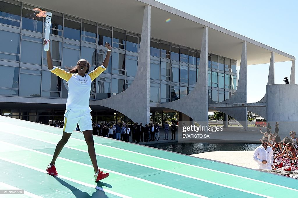 Brazilian volleyball player Fabiana Claudino carries the Olympic torch at Planalto Palace in Brasilia following the flame's arrival in the country on May 3, 2016 ahead of the Rio 2016 Olympic Games in August. The Olympic flame arrived in Brasilia May 3 aboard a flight from Geneva to embark on a procession across Brazil culminating in the opening ceremony of the 2016 Games in Rio de Janeiro. The torch will travel to more than 300 towns and cities carried by some 12,000 relay runners before arriving August 5 at the mythic Maracana stadium to kick off the first Olympics in South America. / AFP / EVARISTO SA