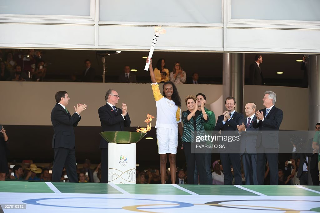 Brazilian volleyball player Fabiana Claudino holds the Olympic flame next to Brazilian President Dilma Rousseff (4-L) at Planalto Palace in Brasilia following its arrival from Geneva on May 3, 2016, beginning the flame's journey across the country before the start of the 2016 Olympic Games on August 5. The Olympic flame arrived in Brasilia May 3 aboard a flight from Geneva to embark on a procession across Brazil culminating in the opening ceremony of the 2016 Games in Rio de Janeiro. The torch will travel to more than 300 towns and cities carried by some 12,000 relay runners before arriving August 5 at the mythic Maracana stadium to kick off the first Olympics in South America. / AFP / EVARISTO SA