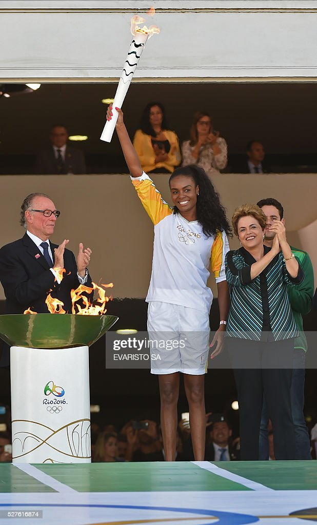 Brazilian volleyball player Fabiana Claudino holds the Olympic torch next to Brazilian President Dilma Rousseff (4-L) at Planalto Palace in Brasilia following the flame's arrival in Brazil on May 3, 2016, to begin it's journey across the country before the start of the 2016 Olympic Games on August 5. The Olympic flame arrived in Brasilia May 3 aboard a flight from Geneva to embark on a procession across Brazil culminating in the opening ceremony of the 2016 Games in Rio de Janeiro. The torch will travel to more than 300 towns and cities carried by some 12,000 relay runners before arriving August 5 at the mythic Maracana stadium to kick off the first Olympics in South America. / AFP / EVARISTO SA