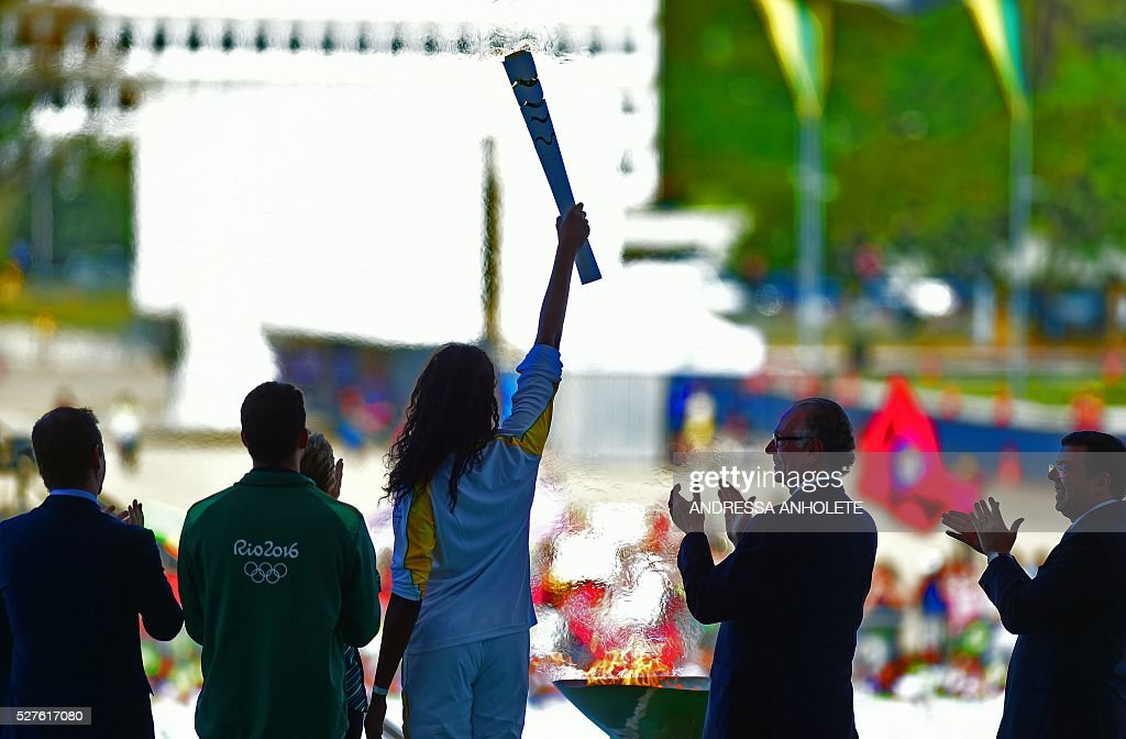 Brazilian volleyball player Fabiana Claudino holds the Olympic torch after receiving it from Brazilian President Dilma Rousseff at Planalto Palace in Brasilia following the flame's arrival in Brazil on May 3, 2016, to begin it's journey across the country before the start of the 2016 Olympic Games on August 5. The Olympic flame arrived in Brasilia May 3 aboard a flight from Geneva to embark on a procession across Brazil culminating in the opening ceremony of the 2016 Games in Rio de Janeiro. The torch will travel to more than 300 towns and cities carried by some 12,000 relay runners before arriving August 5 at the mythic Maracana stadium to kick off the first Olympics in South America. / AFP / ANDRESSA