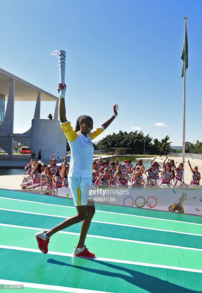 Brazilian volleyball player Fabiana Claudino holds the Olympic torch after receiving it from Brazilian President Dilma Rousseff at Planalto Palace in Brasilia following the flame's arrival in Brazil on May 3, 2016, to begin it's journey across the country before the start of the 2016 Olympic Games on August 5. The Olympic flame arrived in Brasilia May 3 aboard a flight from Geneva to embark on a procession across Brazil culminating in the opening ceremony of the 2016 Games in Rio de Janeiro. The torch will travel to more than 300 towns and cities carried by some 12,000 relay runners before arriving August 5 at the mythic Maracana stadium to kick off the first Olympics in South America. / AFP / EVARISTO SA