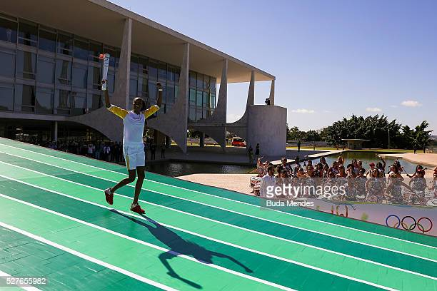 Brazilian volleyball player Fabiana Claudino holds the Olympic torch after receiving it from Brazilian President Dilma Rousseff at Planalto Palace in...