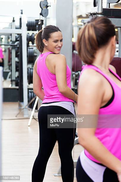 Brazilian woman checking out her butt at the gym