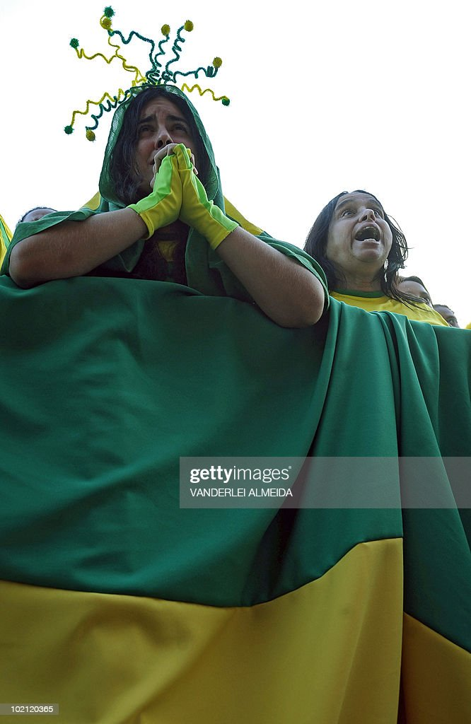A Brazilian woman prays as she watches the FIFA World Cup South Africa 2010 football match between Brazil and North Korea on a giant screen in Copacabana beach, in Rio de Janeiro, Brazil on June 15, 2010.