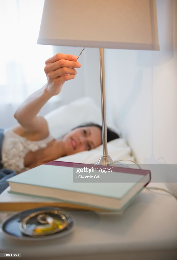 Brazilian woman turning of lamp in bedroom