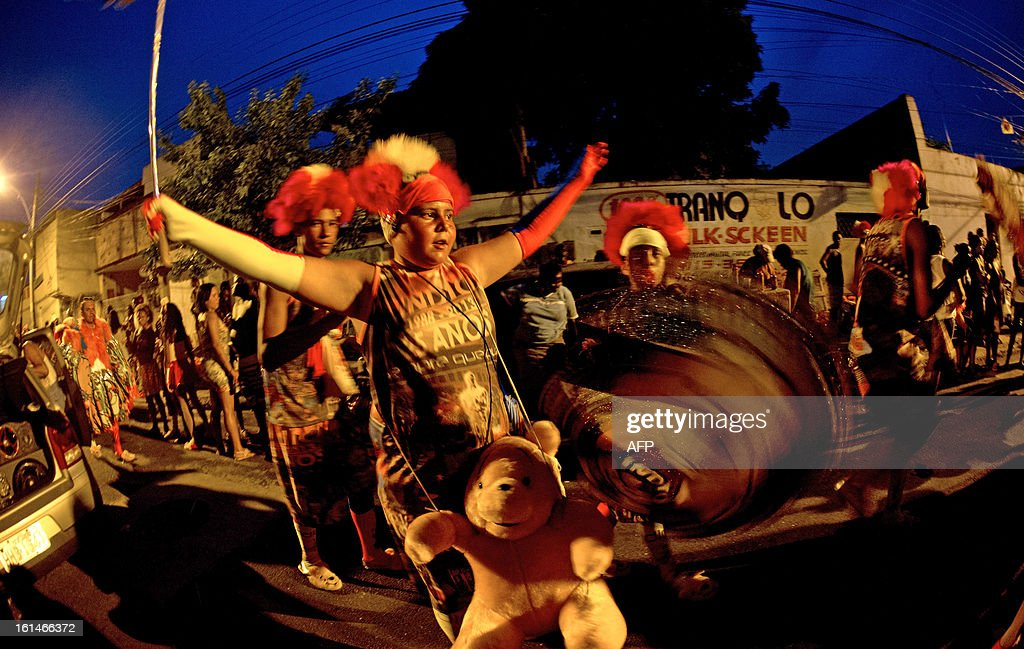 brazilian's group 'Indio' from Guadalupe slum, north surbub of Rio, arrive at a football field wearing their carnival suits for the 'Bate bola' popular Carnival in Rio de Janeiro on february 10, 2013. AFP PHOTO / Christophe Simon