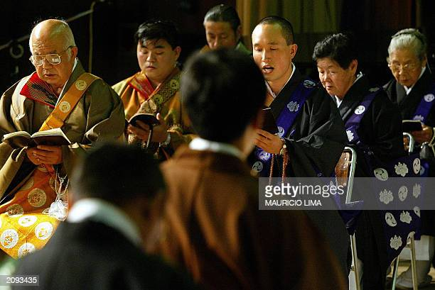 Brazilians of Japanese origin sing during a Buddhist ceremony honouring defunct immigrants as part of the celebrations of the 95th anniversary of the...