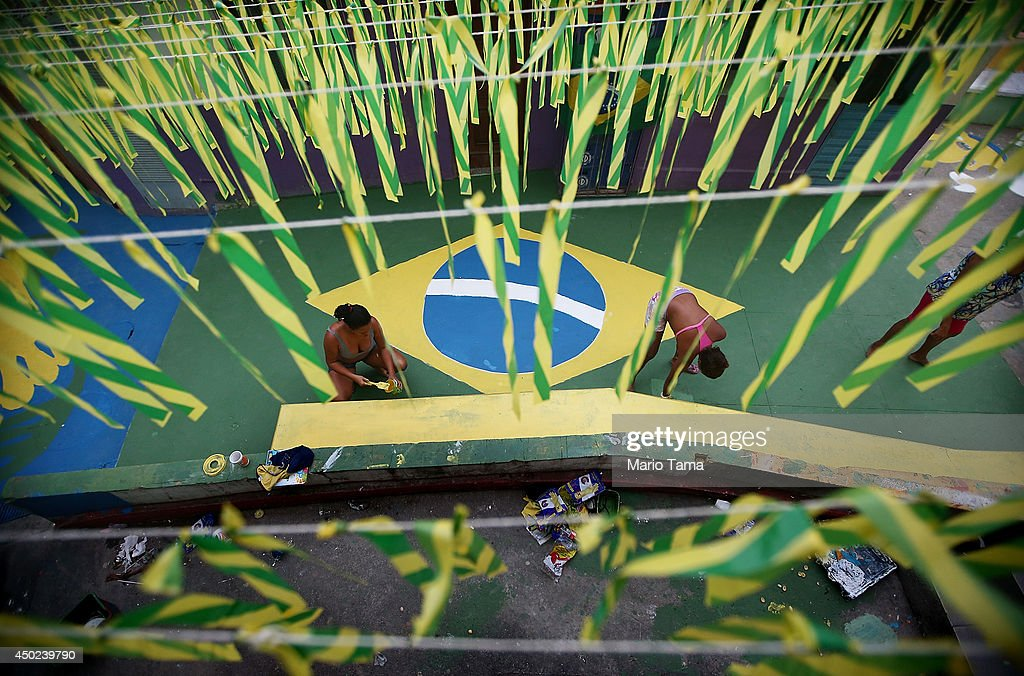 Brazilians paint a section of the Santa Marta shantytown, or 'favela', in Brazilian colors on June 7, 2014 in Rio de Janeiro, Brazil. A Brazilian paint company donated the supplies. Brazil is in final preparations to host the 2014 FIFA World Cup which kicks off June 12.