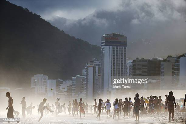 Brazilians play altinha a spinoff of soccer played on the beach as others gather on Ipanema Beach in a lowlying mist on April 21 2014 in Rio de...
