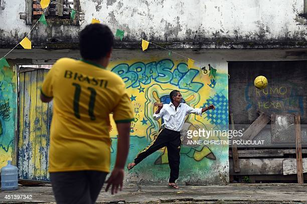 Brazilians play football in Porto Seguro on June 28 during the Round of 16 football match between Brazil and Chile played at the Mineirao Stadium in...
