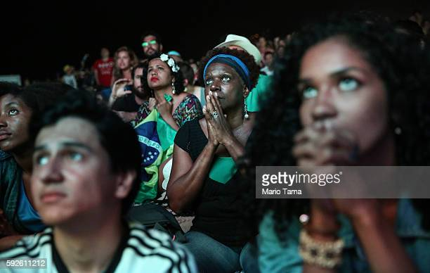 Brazilians watch during the second half before their team defeated Germany to win the soccer gold medal during the Rio 2016 Olympic Games while...