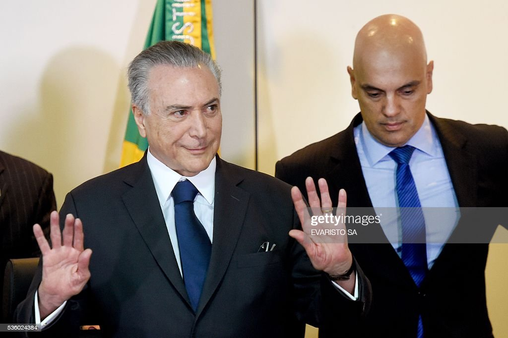 Brazil's acting President Michel Temer (L) and Justice Minister Alexandre de Moraes arrive for a meeting with the secretaries of security of Brazilian states, in Brasilia, on May 31, 2016. Temer proposed a 'joint effort' to 'ban' violence against women following two gang rapes of teenage girls including one in Rio de Janeiro supposedly involving 30 men that was filmed and posted online and that has shocked Brazil. / AFP / EVARISTO SA