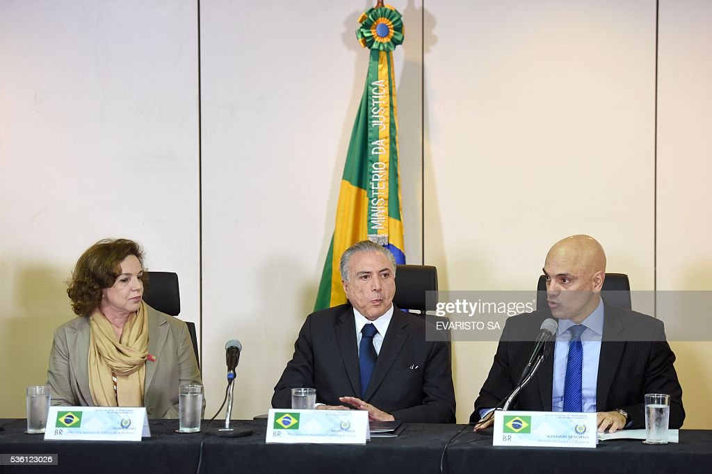 Brazil's acting President Michel Temer (C) gestures between National Secretary of Policy for Women Fatima Pelaes (L) and Justice Minister Alexandre de Moraes during a meeting with secretaries of security from all Brazilian states in Brasilia, Brazil, May 31, 2016. Temer proposed 'joint effort' to 'ban' violence against women after the case of an adolescent victim of gang rape in Rio de Janeiro. / AFP / EVARISTO SA
