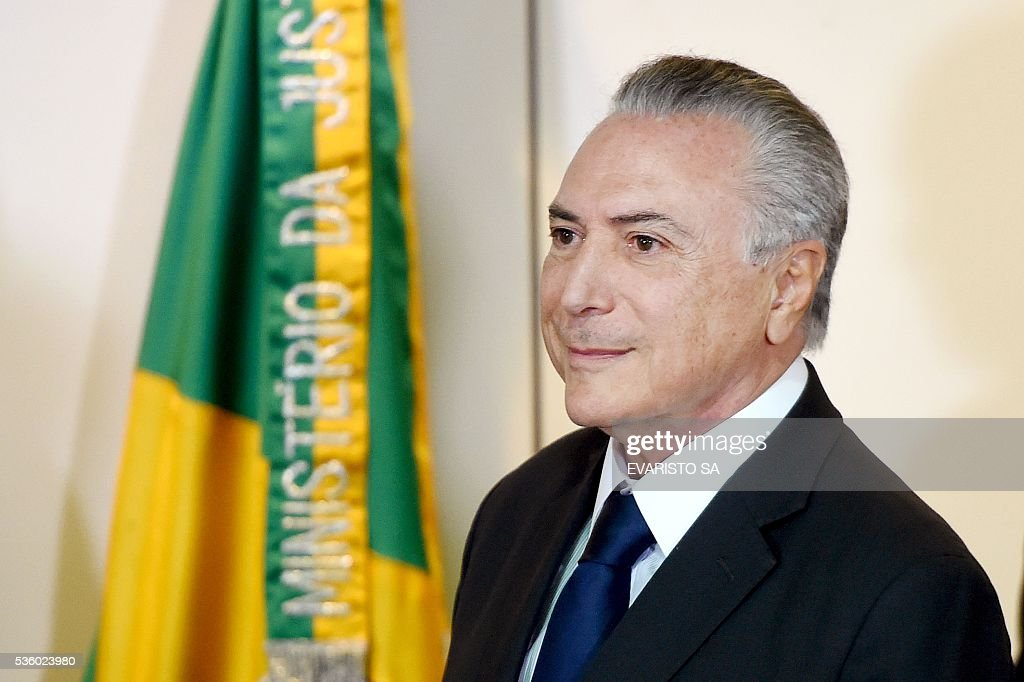 Brazil's acting President Michel Temer is pictured during a meeting with the secretaries of security of Brazilian states, in Brasilia, on May 31, 2016. Temer proposed a 'joint effort' to 'ban' violence against women following two gang rapes of teenage girls including one in Rio de Janeiro supposedly involving 30 men that was filmed and posted online and that has shocked Brazil. / AFP / EVARISTO SA