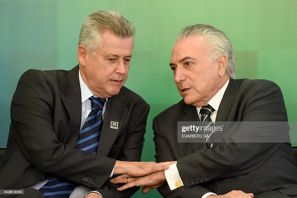 Brazil's acting President Michel Temer (R) talks to Federal District Governor Rodrigo Rollenberg during the ceremony to announce the increase of the Bolsa Familia (Income Distribution Program) and the release of funds for education at the Planalto Palace in Brasilia on June 29, 2016. The government announced an average increase of 12.5% in the Bolsa Familia program, following two years without adjustment. / AFP / EVARISTO SA