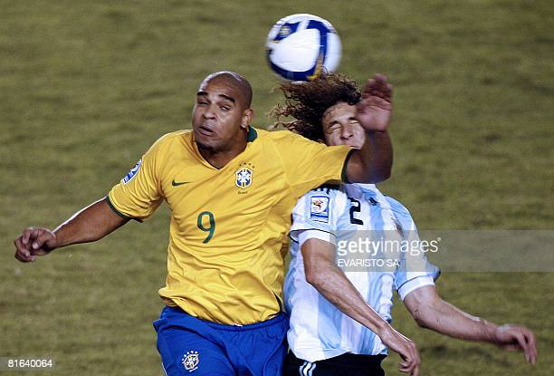 Brazil's Adriano heads the ball with Argentina's Fabricio Coloccini during their FIFA World Cup South Africa2010 qualifier football match on June 18...