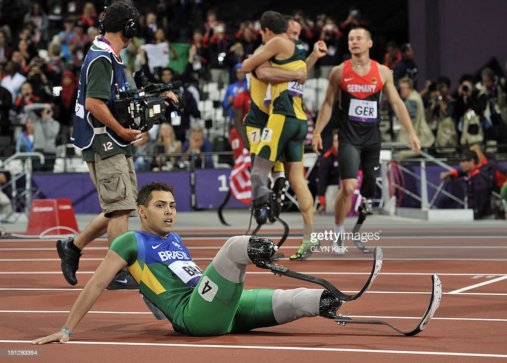 Brazil's Alan Fonteles Cardoso Oliveira sits on the track as South Africa's Oscar Pistorius (C back) and the South Africa team celebrate at the end of the men's 4x100 metres relay T42-46 final during the athletics competition at the London 2012 Paralympic Games at the Olympic Stadium in east London on September 5, 2012. South Africa won in the world record time of 41.78, the team from Brazil were disqualified. AFP PHOTO / GLYN KIRK