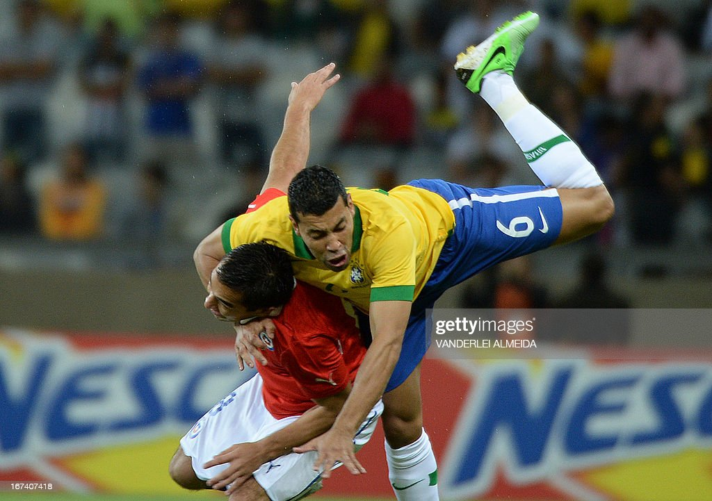 Brazil's Andre Santo (R) vies for the ball with Cristian Fernando Meneses of Chile, during their friendly football match at the Mineirao stadium, in Belo Horizonte, Minas Gerais on April 24, 2013.