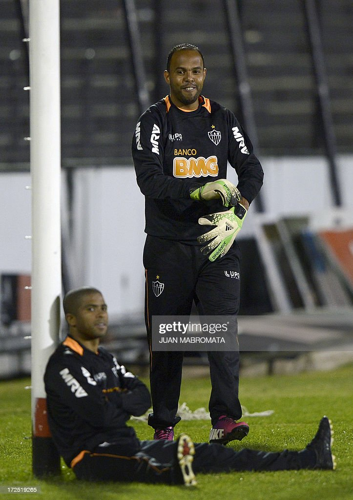 Brazil's Atletico Mineiro forward Alecsandro (back) jokes wearing the gloves of a teammate next to defender Junior Cesar during a training session at Marcelo Bielsa stadium in Rosario, some 350 km north of Buenos Aires, Argentina, on July 2, 2013 on the eve of the Copa Libertadores 2013 semifinal first leg football match against Argentina's Newell's Old Boys. AFP PHOTO / Juan Mabromata