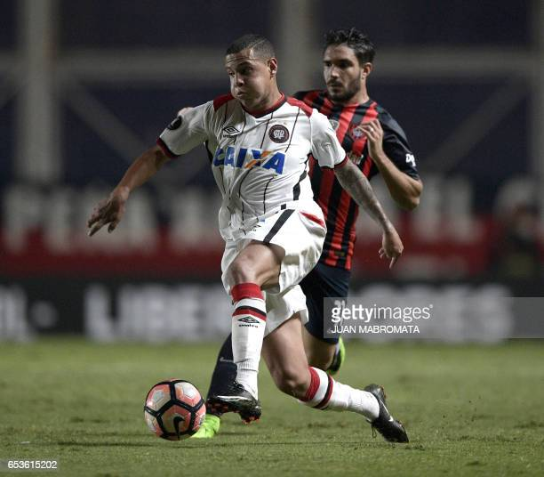 Brazil's Atletico Paranaense defender Sidcley vies for the ball with Argentina's San Lorenzo forward Ezequiel Cerutti during their Copa Libertadores...