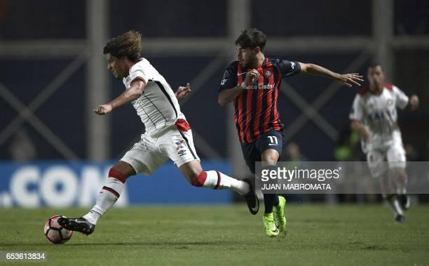 Brazil's Atletico Paranaense midfielder Felipe Gedoz vies for the ball with Argentina's San Lorenzo forward Ezequiel Cerutti during their Copa...