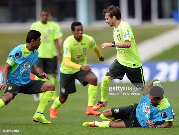 Brazil's Bernard jumps over Daniel Alves during a training session of the Brazilian national football team at the squad's Granja Comary training...
