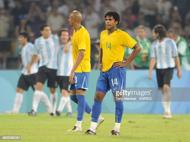 Brazil's Breno and Ilsinho stand dejected as Argentina celebrate Juan Riquelme scoring his sides thied goal of the game