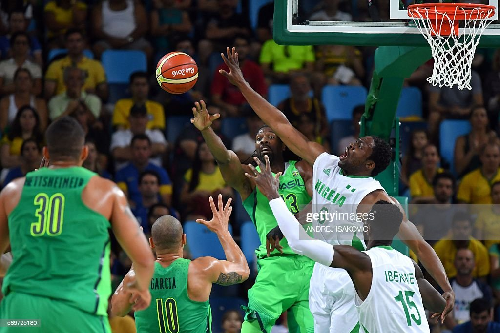 Brazil's centre Nene Hilario pass under pressure from Nigeria's power forward Ike Diogu during a Men's round Group B basketball match between Nigeria...