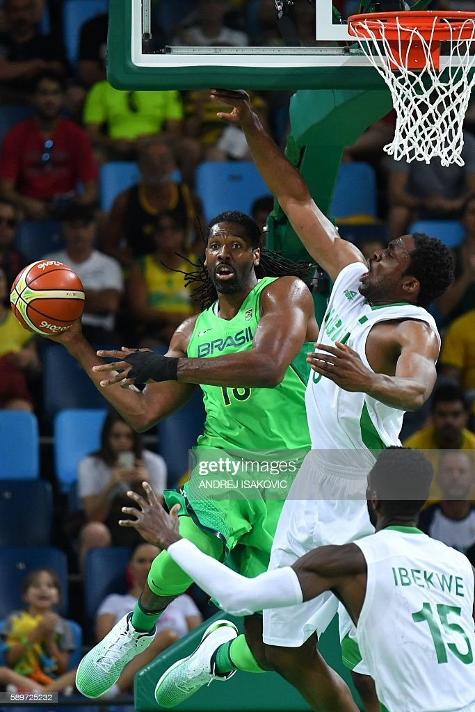 Brazil's centre Nene Hilario passes the ball under pressure from Nigeria's power forward Ike Diogu during a Men's round Group B basketball match...