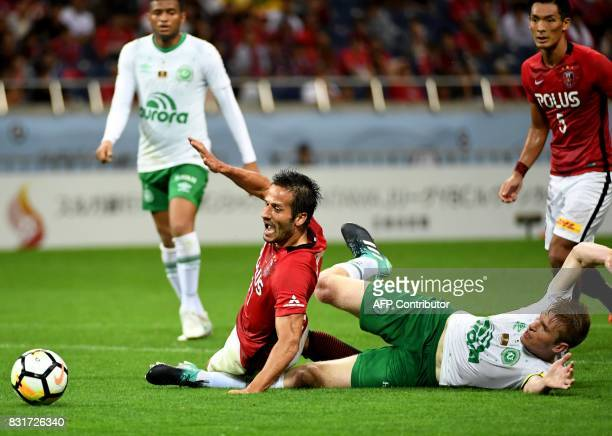 Brazil's Chapecoense FC captain and defender Grolli fouls Japan's Urawa Reds forward Zlatan for a penalty kick during their football friendly match...