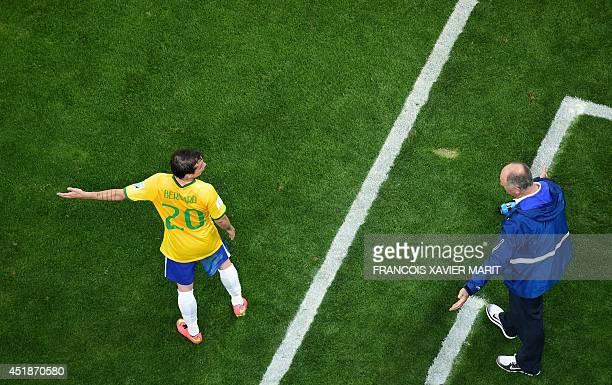 Brazil's coach Luiz Felipe Scolari talks to Brazil's forward Bernard during the semifinal football match between Brazil and Germany at The Mineirao...