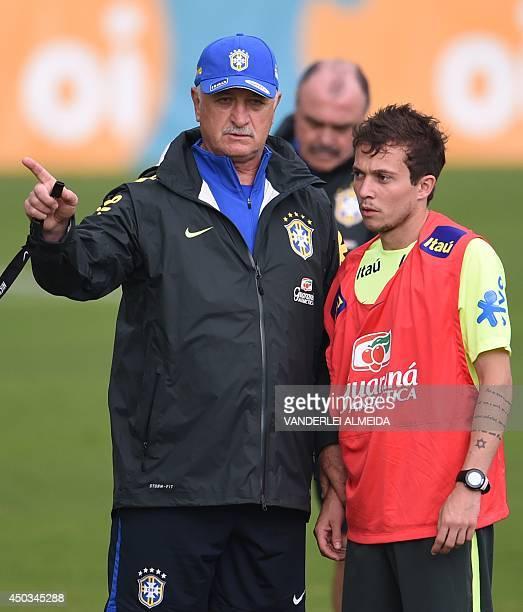 Brazil's coach Luiz Felipe Scolari talks to strike Bernard during a training session of the Brazilian national football team at the squad's Granja...