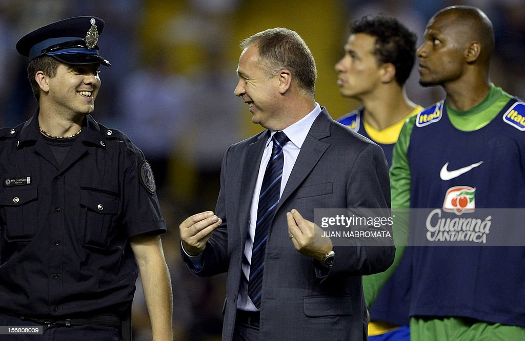 Brazil's coach Mano Menezes (C) jokes with a policeman before the start of the Americas Super Derby second leg match against Argentina at Bombonera stadium in Buenos Aires on November 21, 2012. AFP PHOTO / Juan Mabromata