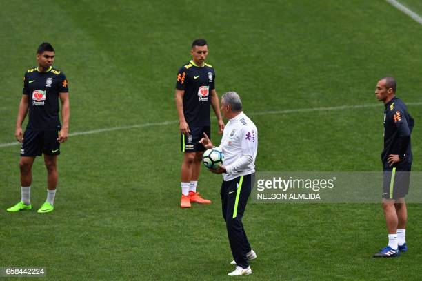 Brazil's coach Tite gives instructions to players Casemiro Marquinhos and Miranda during a training session on the eve of their 2018 FIFA Russia...