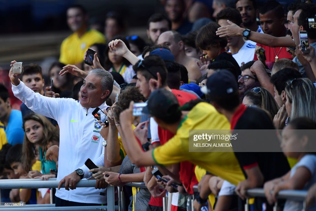 Brazil's coach Tite (L) poses with fans after a training session at the Morumbi stadium in Sao Paulo, Brazil on March 25, 2017 ahead of a 2018 FIFA World Cup qualifier match against Paraguay on March 28 in Sao Paulo, Brazil. /