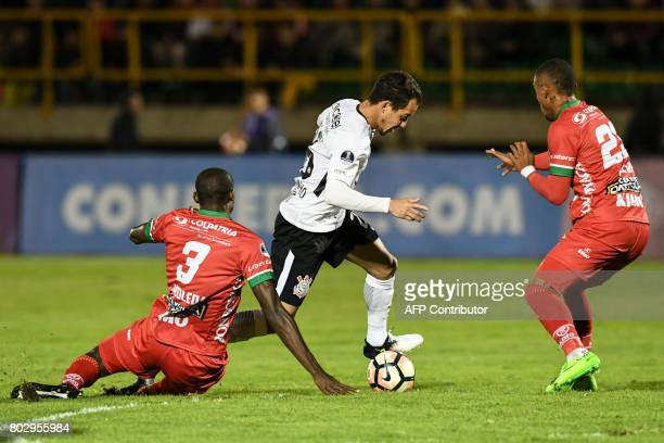Brazil's Corinthians midfielder Rodriguinho controls the ball between Colombia's Patriotas midfielder Danilo Arboleda and Colombia's Patriotas...