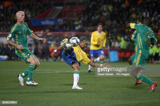 Brazil's De Souza Robinho has a shot on goal under pressure from South Africa's Matthew Booth and Aaron Mokoena