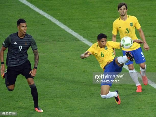 Brazil's defender Douglas Santos controls the ball next to Brazil's defender Rodrigo Caio and Germany's forward Davie Selke during the Rio 2016...