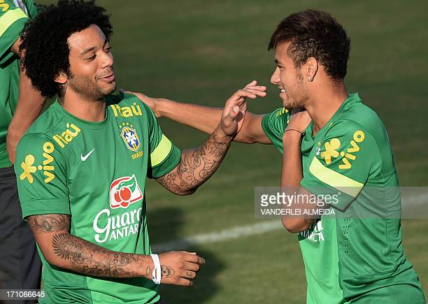 Brazil's defender Marcelo and forward Neymar chat during a training session at the Roberto Santos stadium in Salvador northeastern Brazil on the eve...