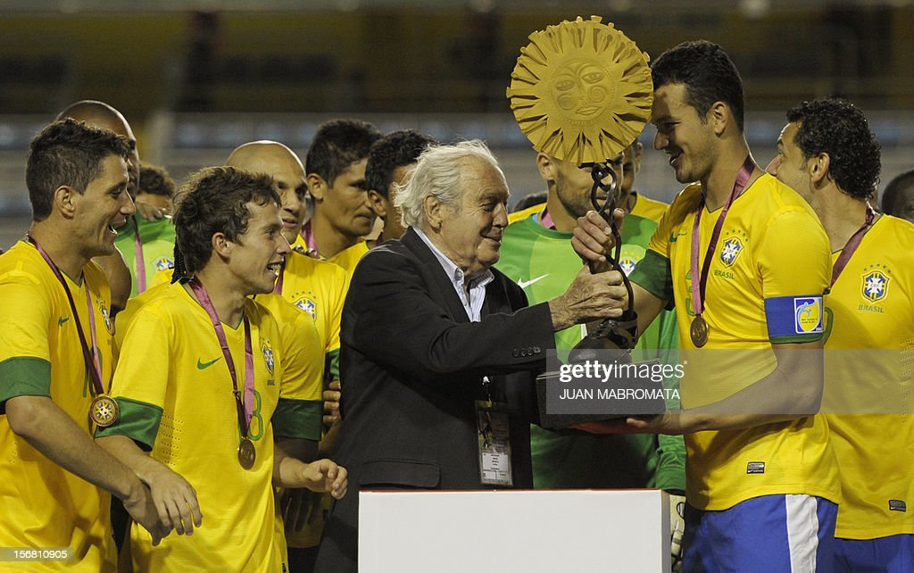 Brazil's defender Rever (2R) receives the trophy from Uruguayan artist Carlos Paez Vilaro (C) during the award ceremony after defeating Argentina in penalty shoot-out at a friendly football match at Bombonera stadium in Buenos Aires on November 21, 2012. AFP PHOTO / Juan Mabromata