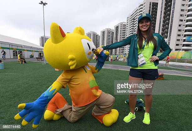 Brazil's epee fencer Amanda Netto Simeao poses for a photograph with the mascot Vinicius at the athletes village of the Rio 2016 Olympic Games in Rio...